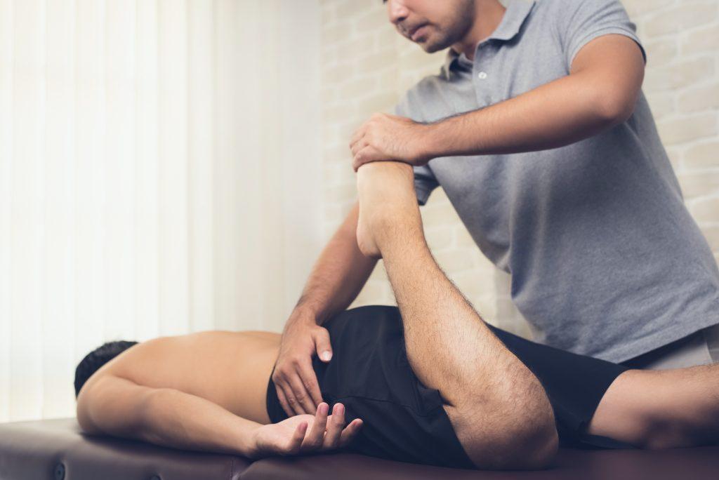 Fisioterapeuta estirando pierna deportista